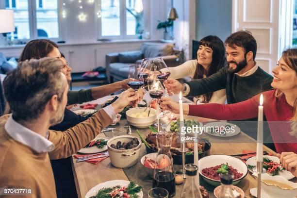 Freunde, die Weingläser im festlichen Weihnachtstisch Klirren