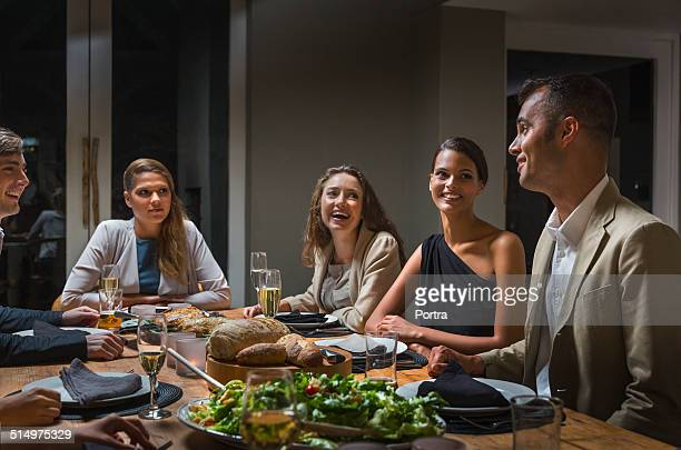 Friends communicating while having dinner at table