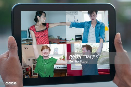 4 friends connecting online, displayed on tablet : Stock Photo