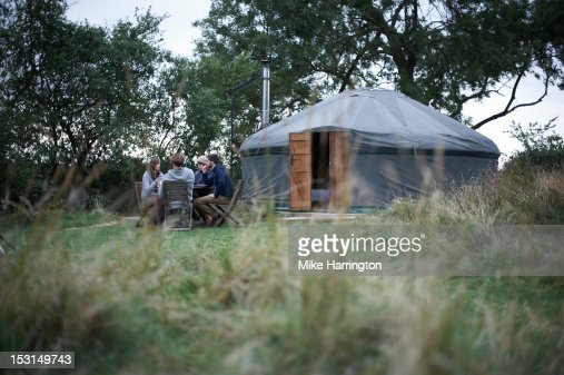 Friends conversing at dining table outside yurt.