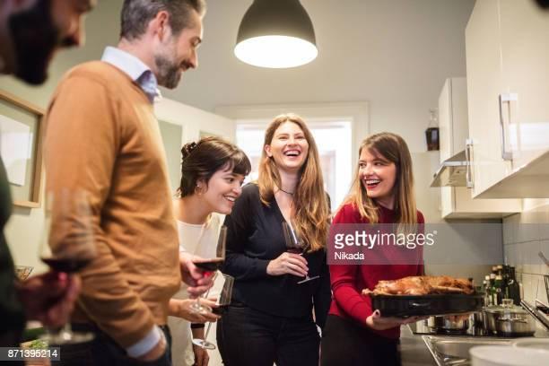 Freunde kochen Geflügel in Küche für Weihnachtsfeier