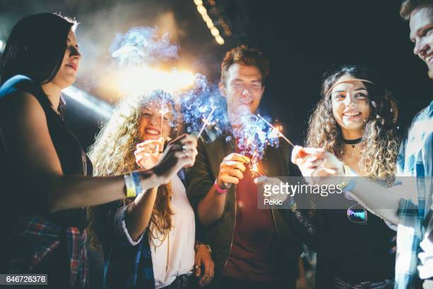 Friends dancing and celebrating with sparklers at night