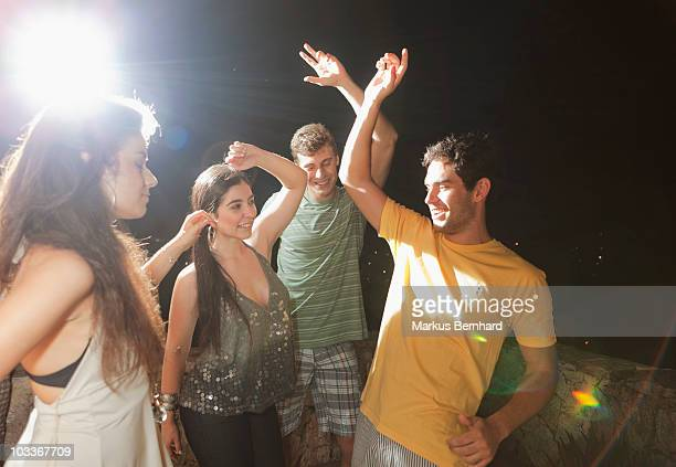 Friends dancing at night at a party.
