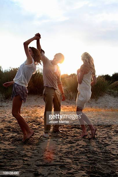 Friends dancing at the beach at sunset