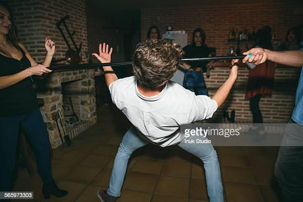 Friends dancing limbo in nightclub