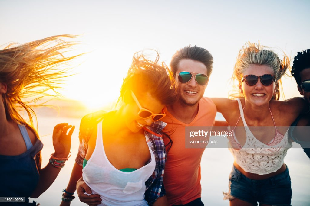 Friends dancing on beach in sunset
