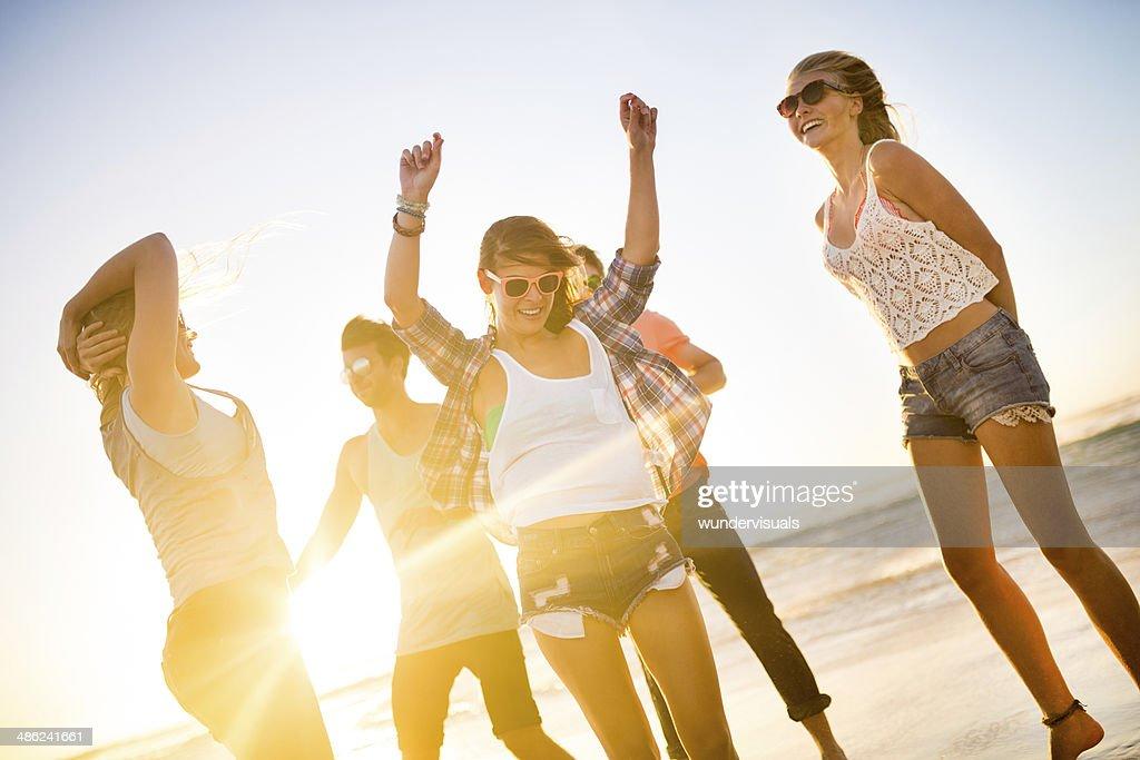 Freunde, Tanzen am Strand bei Sonnenuntergang : Stock-Foto
