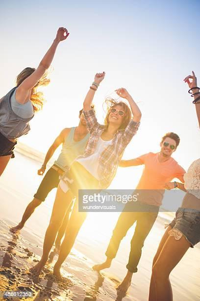 Amici ballare sulla spiaggia al tramonto