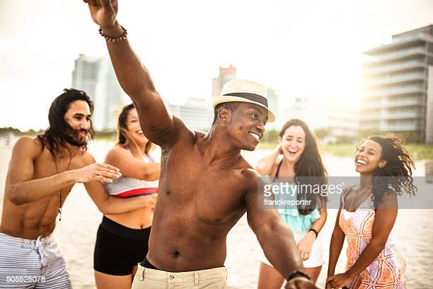 friends dancing on the beach for a party