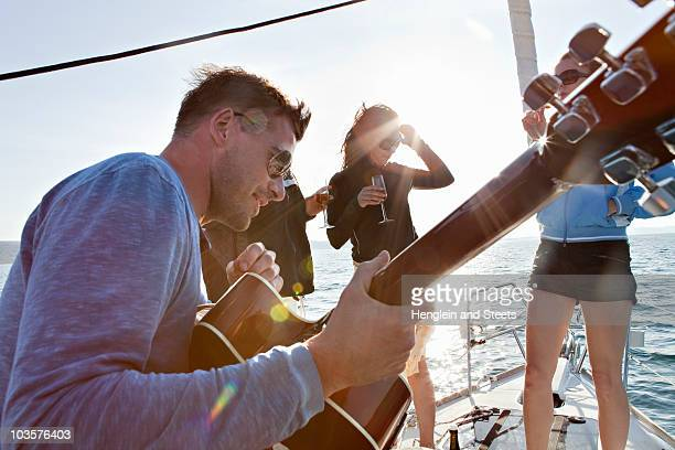 Friends dancing with guitar on yacht