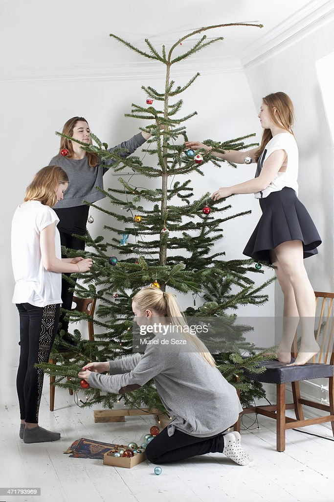 Friends decorating Christmas tree : Stock Photo