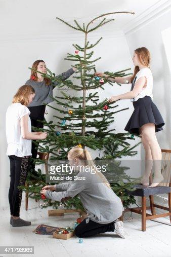 Friends decorating Christmas tree : Stock Photo