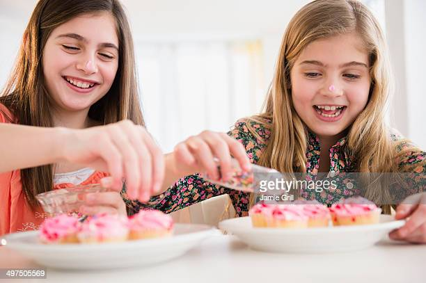 Friends decorating cupcakes together
