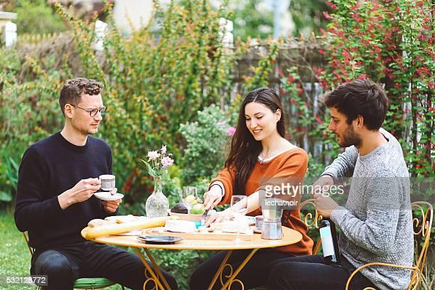 Amigos de una comida en el área suburbana de la ciudad de París al jardín