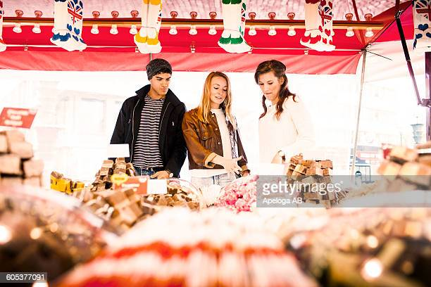 Friends discussing on buying fudge at market