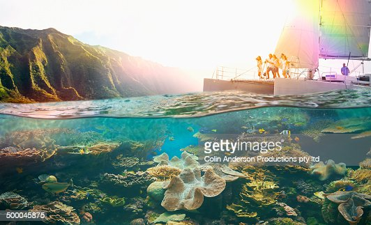 Friends diving off boat into tropical reef