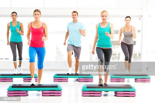 Friends Doing Aerobics Using Stair Steppers In Gym