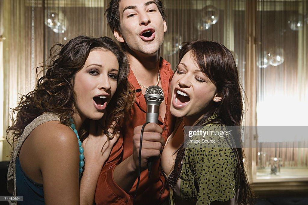 Friends doing karaoke : Stock Photo