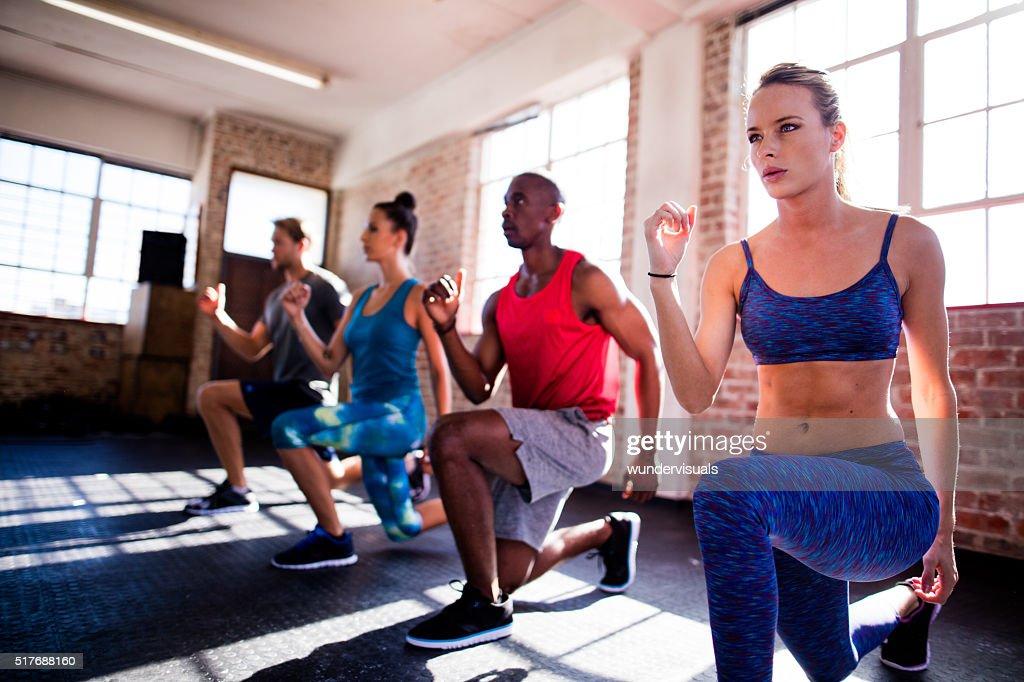 Amis faire des fentes durant une séance d'exercice dans la salle de sport : Photo