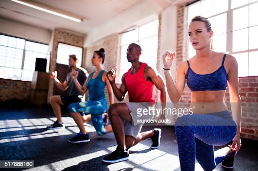 Friends doing lunges during a workout in the gym