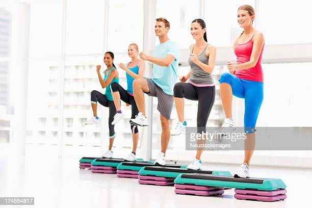 Friends Doing Step Exercise Together In Health Club