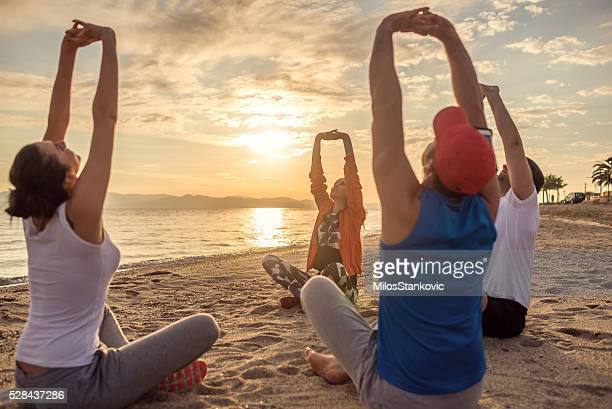 Friends doing yoga exercises at the beach