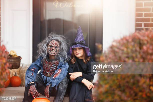 Friends dressed as witch and zombie, sitting on front step of home