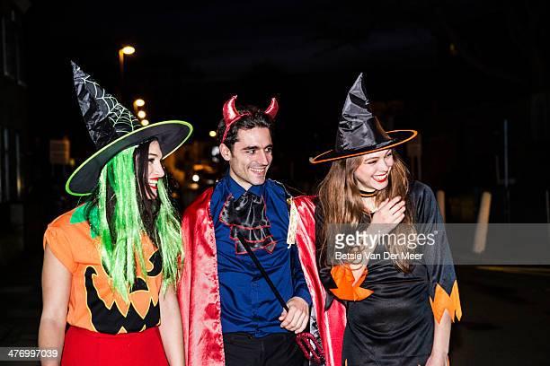 Friends dressed for Halloween,walking on street.