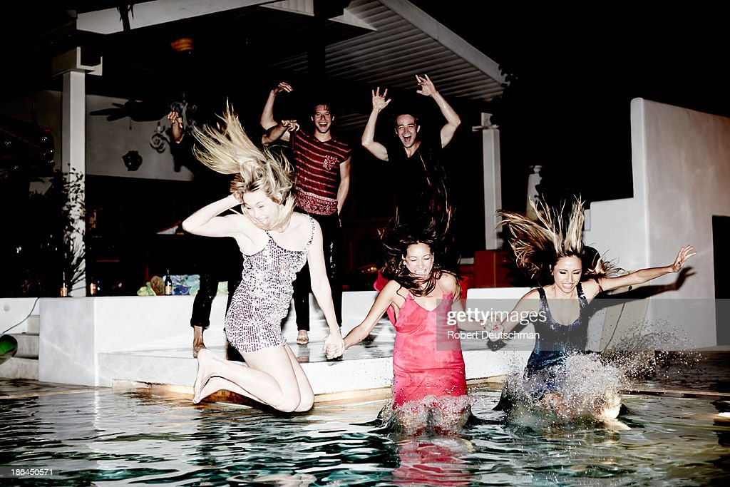 Friends dressed up jumping into the pool at night. : Stock Photo