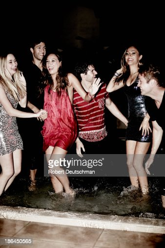 Friends dressed up playing in the pool at night. : Stock Photo