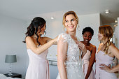 Bride and bridesmaids during the wedding preparations. Friends dressing the bride for wedding in a hotel room.