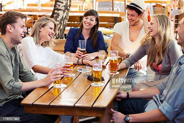 Friends drink and laugh while at a sidewalk cafe
