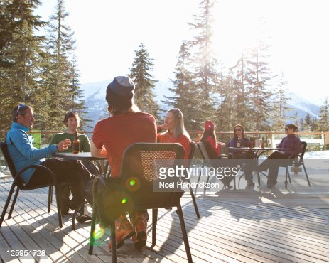 Friends drink beer on ski lodge patio : Stock Photo