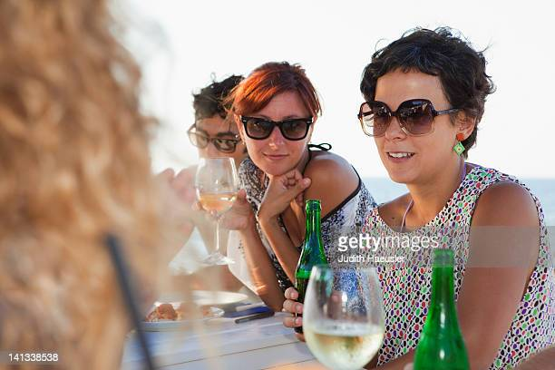 Friends drinking at table outdoors