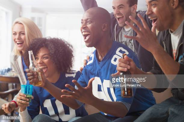 Friends drinking beer and cheering at game on television