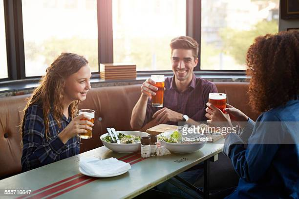 Friends drinking beer and laughing at restaurant