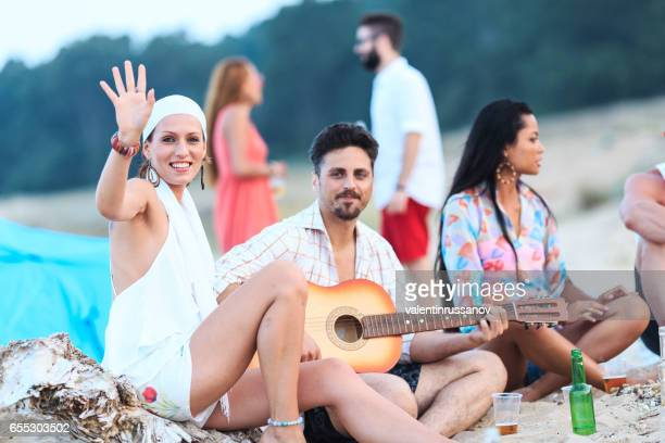Freunde, trinken Bier und Gitarre am Strand