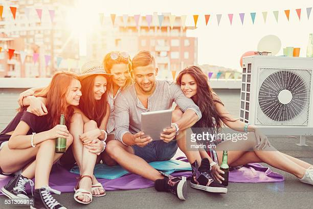 Friends drinking beer and using tablet pc on the rooftop