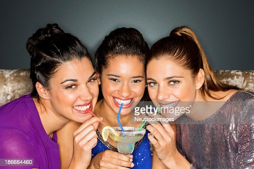 Friends Drinking Cocktail Together Through Straw At Nightclub