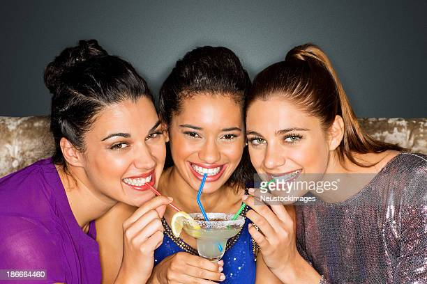 Friends Drinking Cocktail Together Through Straw At Nightclub