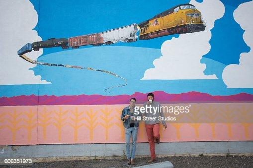 Friends drinking coffee near mural wall
