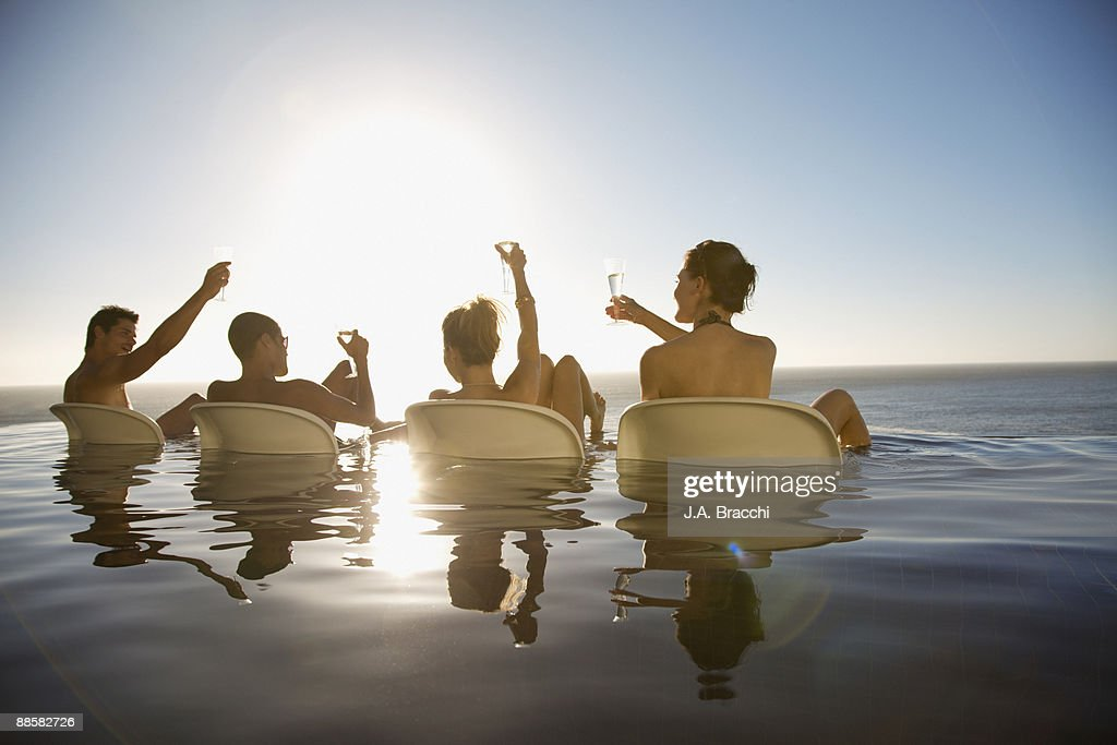 Friends drinking in infinity pool near ocean : Stock Photo