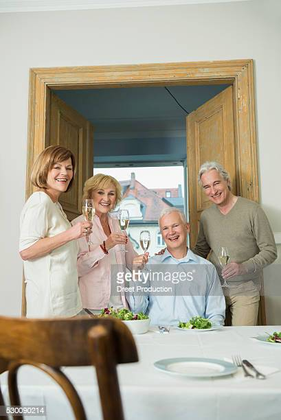 Friends drinking sparkling wine by table, smiling