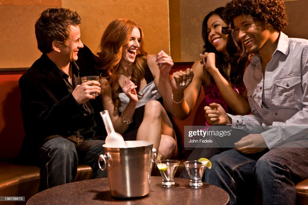 Friends drinking together in nightclub : Stock Photo