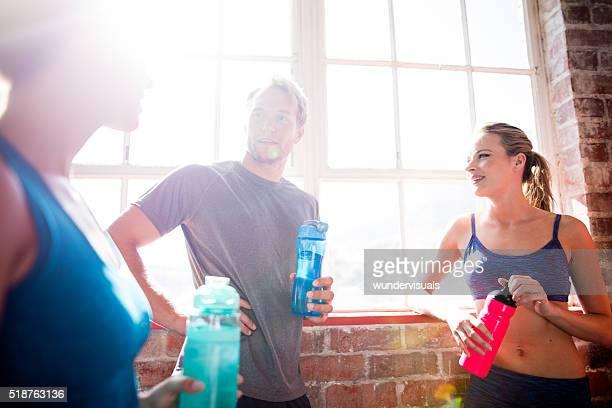 Freunde trinken Wasser und erholen im Fitnessraum
