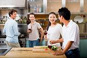 Friends drinking wine in kitchen
