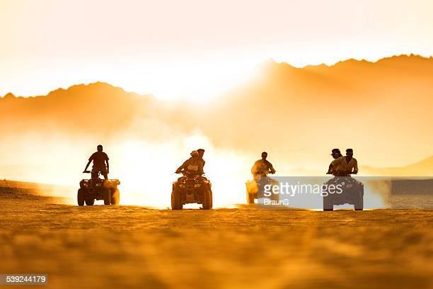 Amici guidano quad moto al tramonto.