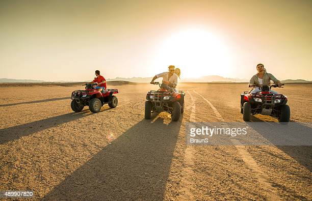 Friends driving quad bikes in the desert at sunset.