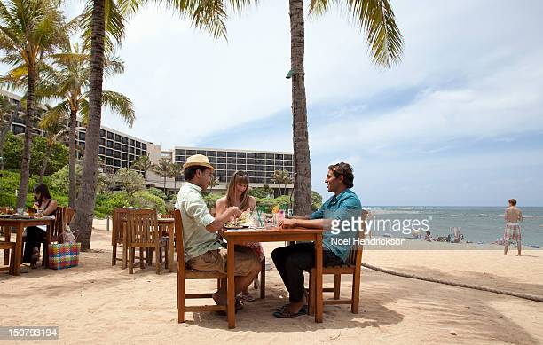 Friends eat a meal at a beachside restaurant