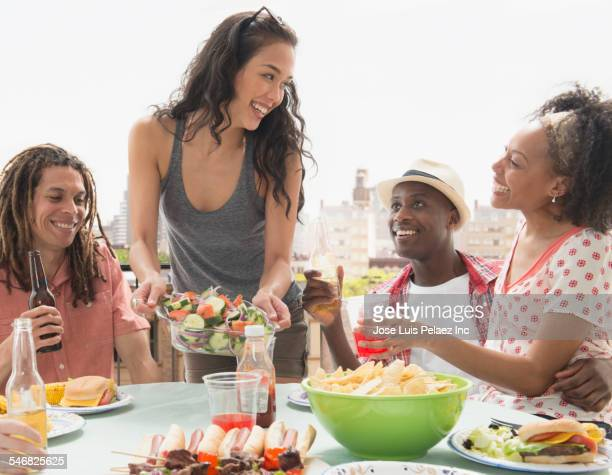 Friends eating at barbecue outdoors
